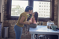 Mother and daughter kissing in kitchen - WESTF22465