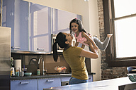Mother lifting daughter in kitchen - WESTF22468
