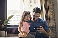 Father with daughter using smart phone in kitchen - WESTF22492