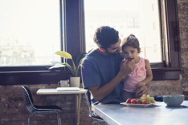 Father feeding daughter in kitchen - WESTF22495
