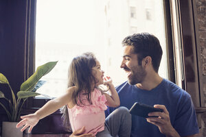 Father with daughter using smart phone in kitchen - WESTF22510