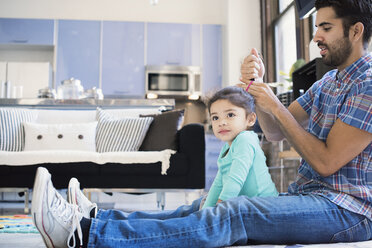 Father sitting on floor doing daughter's hair - WESTF22519