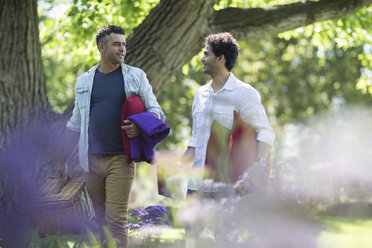 Two friends walking in park with picnic basket and cushions - ZEF12347