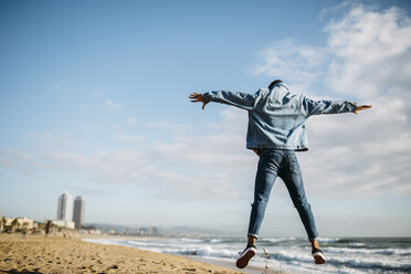 Spain, Barcelona, back view of young man jumping in the air on the beach - JRFF01143