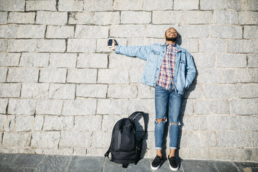 Young man standing in front of a wall holding cell phone - JRFF01152