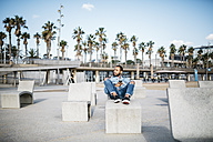 Spain, Barcelona, young man relaxing on beach promenade - JRFF01158
