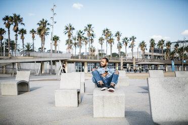 Spain, Barcelona, young man relaxing on beach promenade - JRFF01158