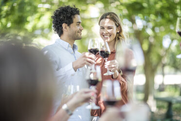 Couple raising a toast together with wine in garden - ZEF12363