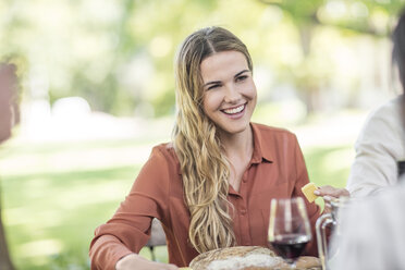 Smiling woman at family lunch in garden - ZEF12372