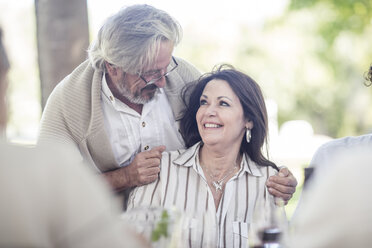 Senior man embracing his wife at outdoor table - ZEF12375