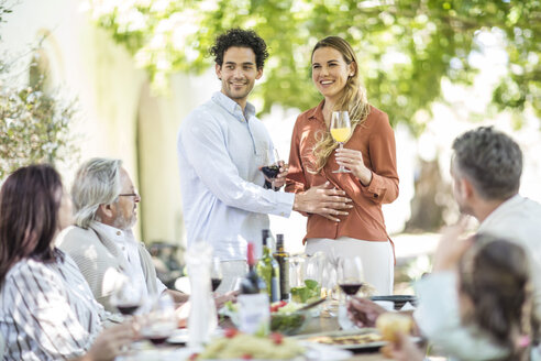Young couple raising a toast with announcement of pregnancy to family during outside family lunch - ZEF12384