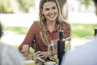 Smiling woman at family lunch in garden - ZEF12387