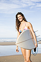Happy woman carrying surfboard on the beach - ABZF01714