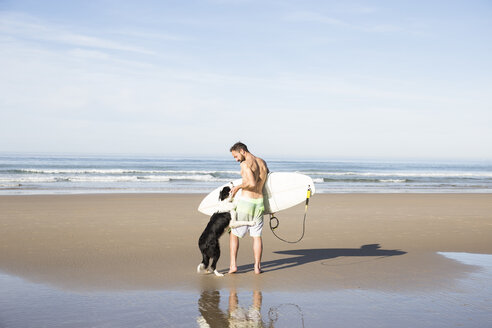 Man with dog and surfboard on the beach - ABZF01720
