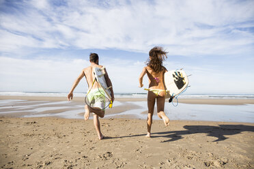 Couple carrying surfboards running on the beach - ABZF01723