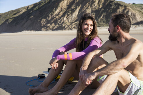 Smiling couple with surfboard sitting on the beach - ABZF01726