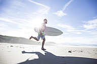 Man carrying surfboard running on the beach - ABZF01729