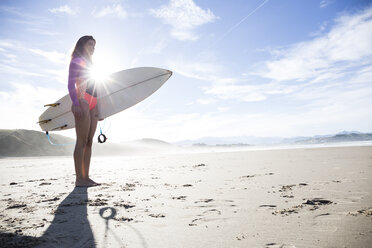 Woman carrying surfboard on the beach - ABZF01732