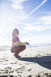 Smiling woman with surfboard crouching on the beach - ABZF01735