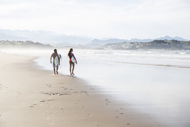 Couple carrying surfboards walking on the beach - ABZF01738