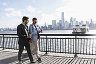 USA, two businessmen walking at New Jersey waterfront with view to Manhattan - UUF09696