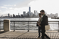 USA, man and woman walking at New Jersey waterfront with view to Manhattan - UUF09699