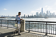 USA, man with cell phone at New Jersey waterfront with view to Manhattan - UUF09708