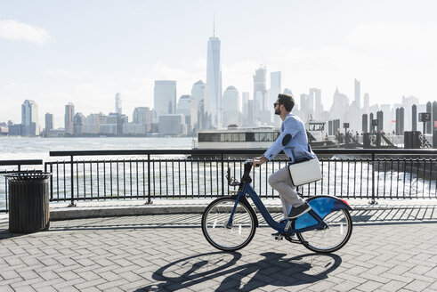 USA, man on bicycle at New Jersey waterfront with view to Manhattan - UUF09717