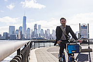 USA, man on bicycle at New Jersey waterfront with view to Manhattan - UUF09720
