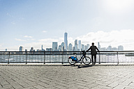 USA, man with bicycle at New Jersey waterfront with view to Manhattan - UUF09723