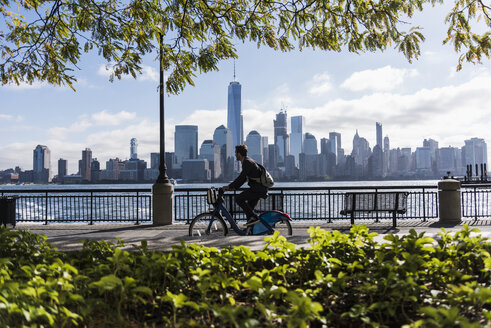 USA, man on bicycle at New Jersey waterfront with view to Manhattan - UUF09726