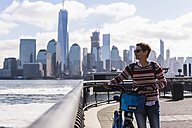 USA, woman with bicycle at New Jersey waterfront with view to Manhattan - UUF09729