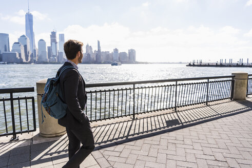 USA, man walking at New Jersey waterfront with view to Manhattan - UUF09732