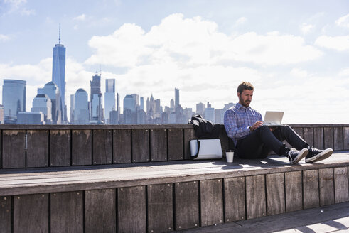 USA, man using tablet at New Jersey waterfront with view to Manhattan - UUF09738