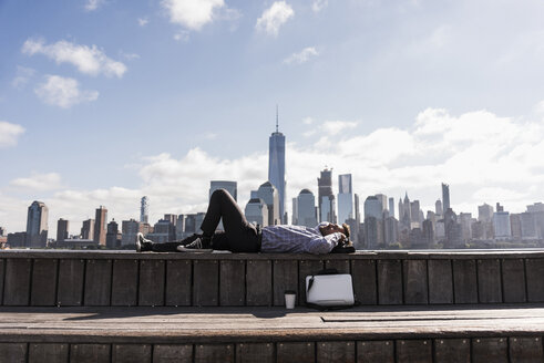 USA, man resting at New Jersey waterfront with view to Manhattan - UUF09741