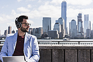 USA, man with headphones and tablet at New Jersey waterfront with view to Manhattan - UUF09750
