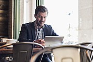 Businessman using tablet in a cafe - UUF09753