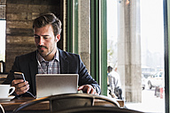 Businessman using tablet and cell phone in a cafe - UUF09756