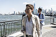 USA, businesswoman with cell phone at New Jersey waterfront with view to Manhattan - UUF09762