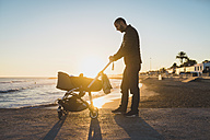 Man with a stroller on the seashore at sunset - GEMF01366