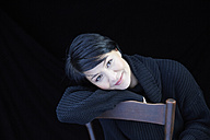 Portrait of smiling woman on chair - FMKF03448