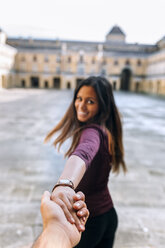 Happy young woman holding hand on urban square - MGOF02750