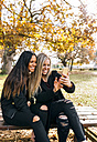 Two smiling young women on park bench looking at cell phone - MGOF02756