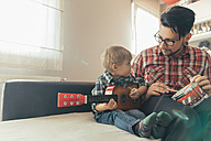 Father and son playing toy musical instruments - ZEDF00481