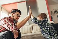 Father and son high fiving - ZEDF00484