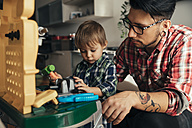 Father and son playing together on toy work bench - ZEDF00487