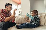 Father and son playing together on couch - ZEDF00490