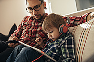 Father and son on couch using tablet and wearing headphones - ZEDF00502
