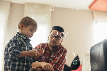 Father and son blowing soap bubbles at home - ZEDF00505