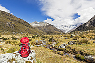 Peru, Andes, Cordillera Blanca, Huascaran National Park, backpack on rock with view to Nevado Huascaran - FOF08536